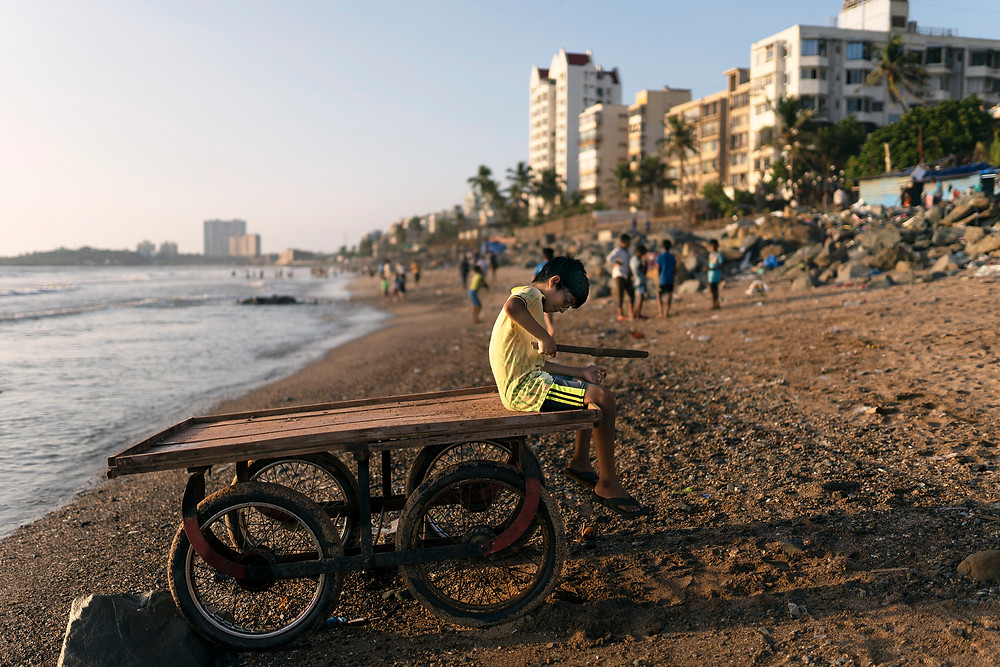 A boy playing on Versova Beach. Mumbai, India.