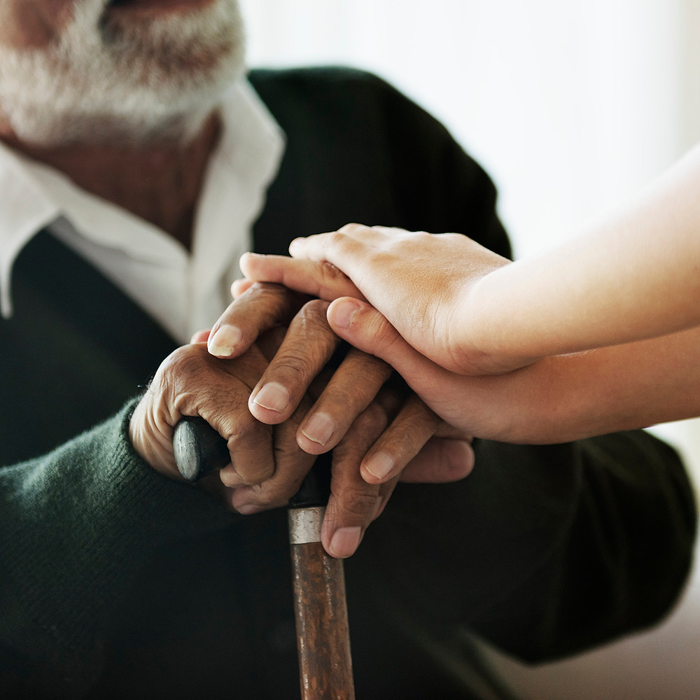 woman helping a black old man who has Parkinson's Disease