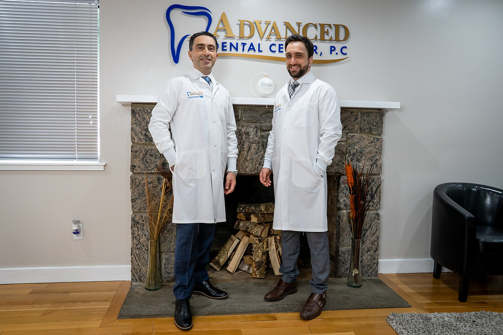two dental doctors in white coat standing smiling