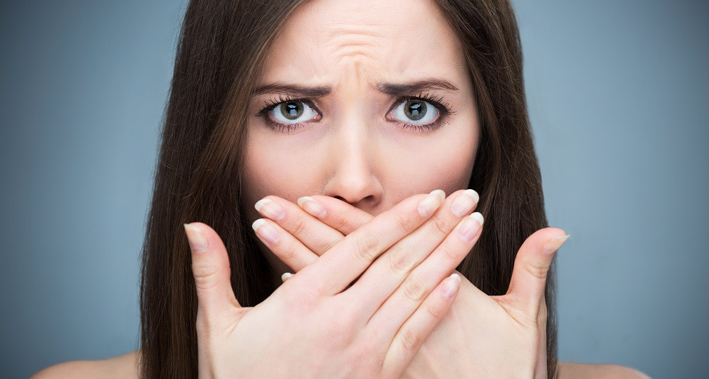 confused women with fear of morning breath, bad breath,  no smile