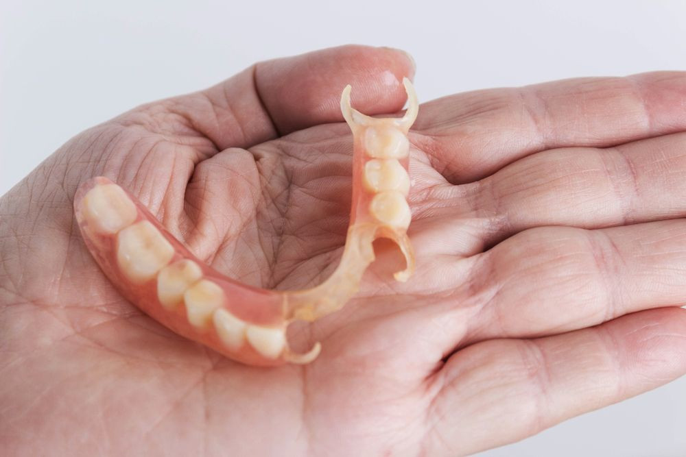 partial denture on palm of senior person