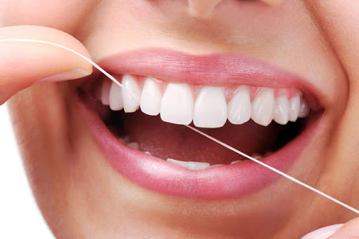 woman flossing her white teeth, beautiful smile