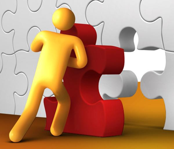 figure of person pushing a puzzle piece in place