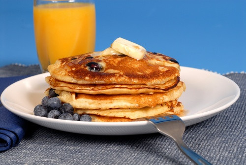 A white plate with a stack of blueberry pancakes and a glass of orange juice.