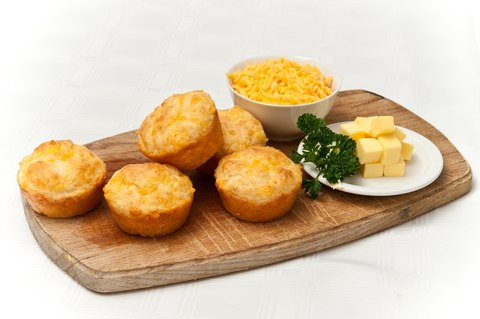 Freshly baked cheese muffins with a bowl of cheese, a plate of butter and parsley, all on a wooden board.