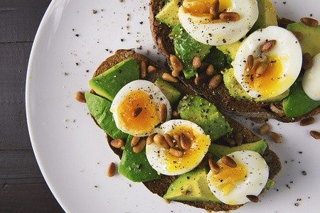 Two slices of brown bread with slices of avocado pear, and boiled egg halves, sprinkled with pine nuts.