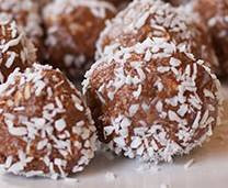 Freshly made no-bake coconut and walnut balls on a kitchen counter.