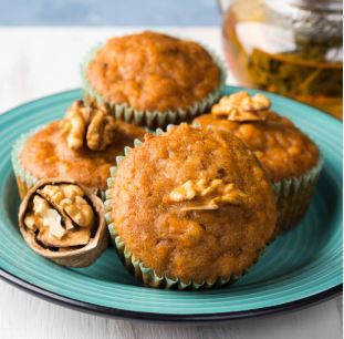 Carrot raisin walnut muffins on a duck-egg blue plate and decorated with walnuts in their shells.
