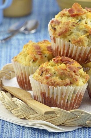 Bacon and cheese muffins on a wicker tray.