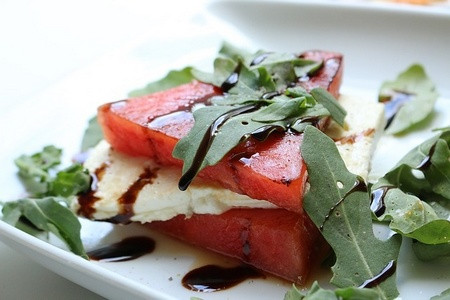 Wedges of watermelon encasing feta cheese on a bed of arugula.