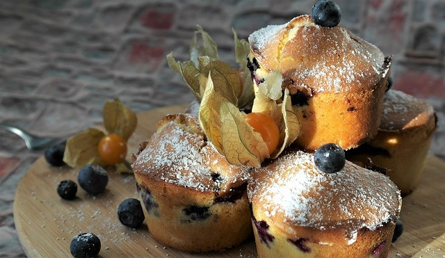 4 blueberry and gooseberry muffins dusted with icing sugar on a wooden board with blueberries scattered around.