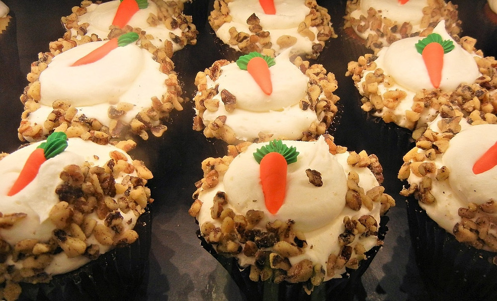 A tray of carrot cake and walnut muffins topped with a healthy frosting.