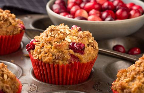 Cranberry oatmeal muffins in red casings with a bowl of fresh cranberries.