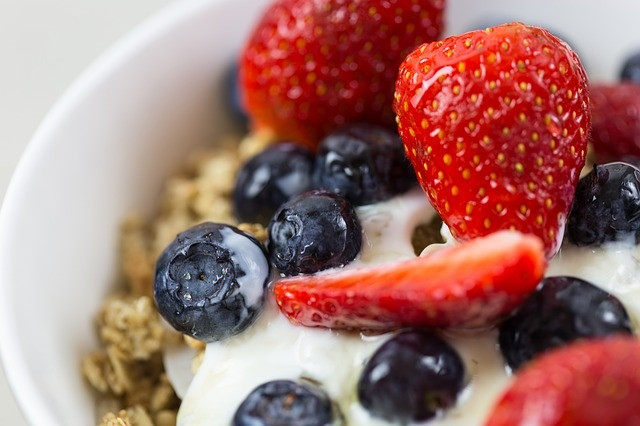 A healthy breakfast of homemade granola, strawberries, blueberries and yogurt.