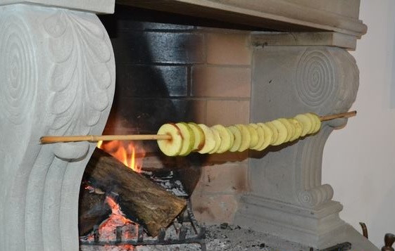 Apple rings on a bamboo stick drying in front of an open fire.