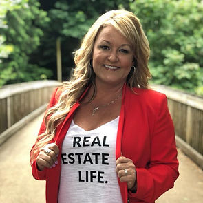 Crystal Meza, Oregon Licensed Realtor wears a red blazer and a t-shirt that says Real Estate Life