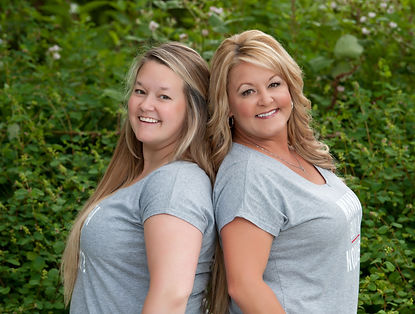 Crystal and Carla, realtors stand with grey t-shirts against green leafy background