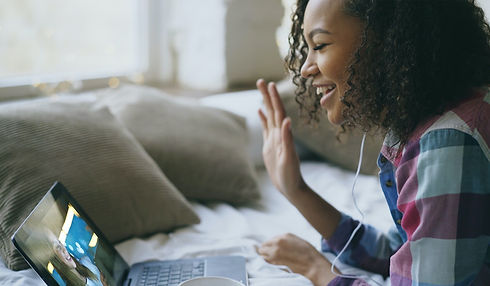 storyblocks-curly-african-american-young-woman-having-video-chat-with-friends-using-laptop-camera-wh