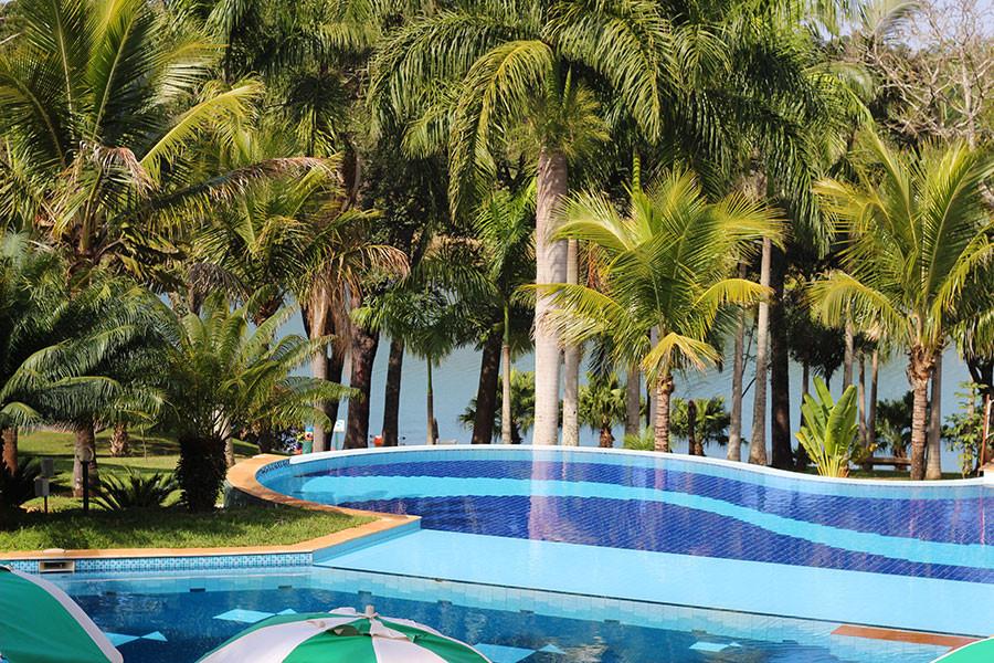 piscina com borda infinita e deck de madeira