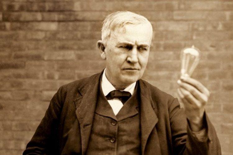 Thomas Edison segurando um bulbo de lâmpada