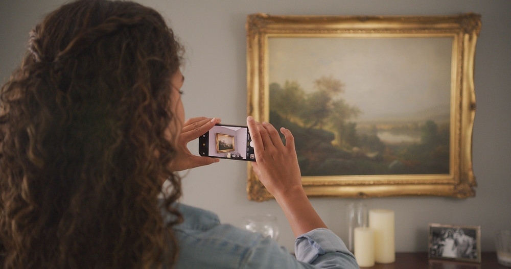 A homeowner takes a picture of her wall art with her phone