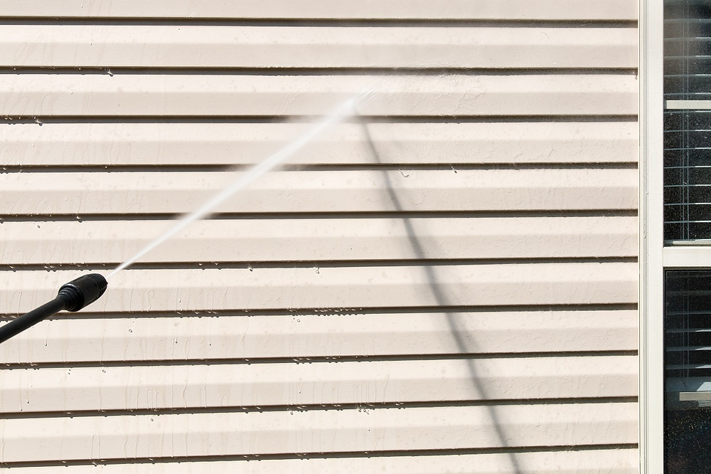 A homeowner cleans off their vinyl siding with a power washer.