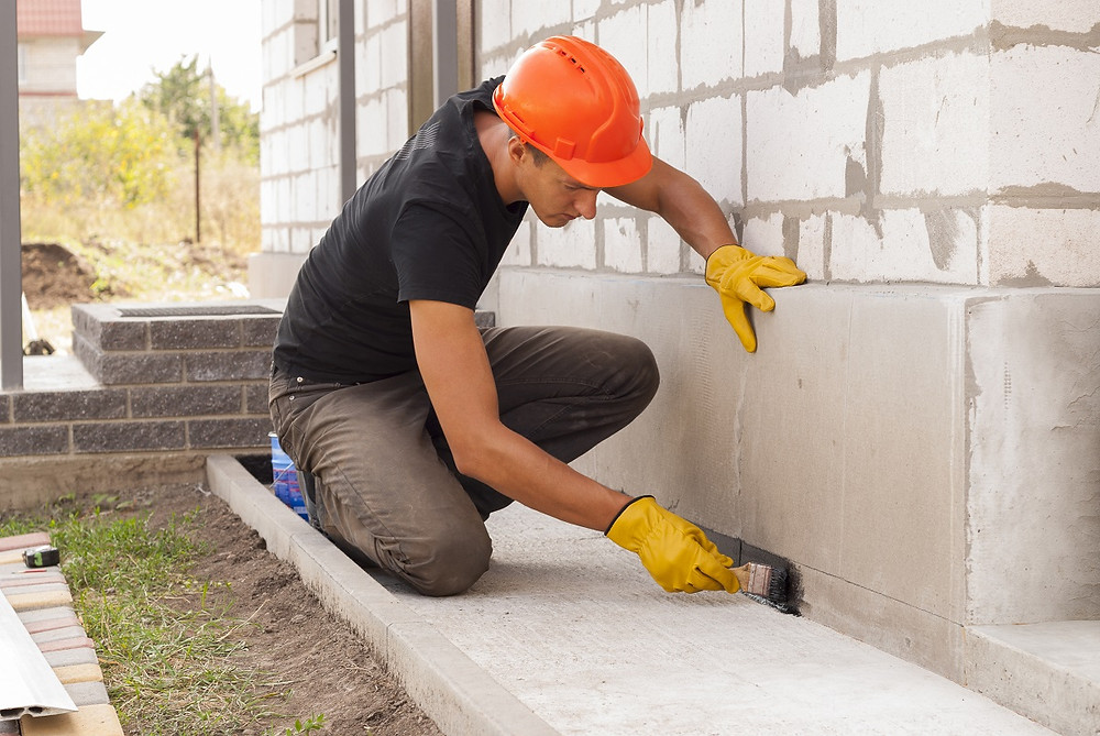 A home professional smooths out the foundation after he finishes filling a crack