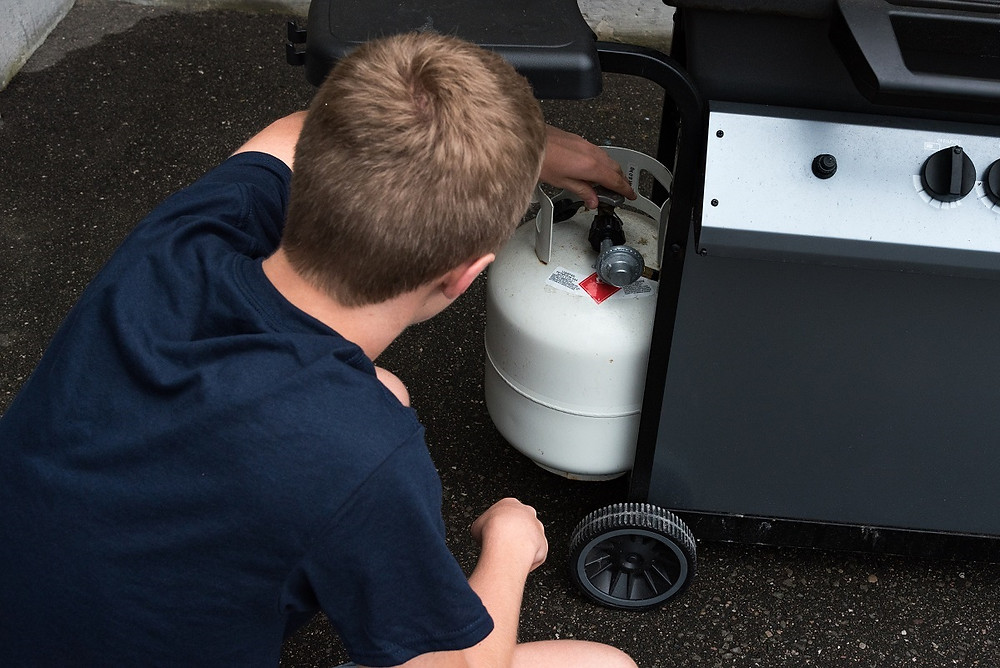 A homeowner checks the gas tank on a grill.