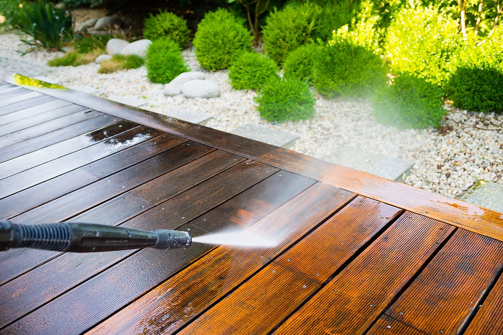A homeowner uses a power washer to clean the boards on a deck.
