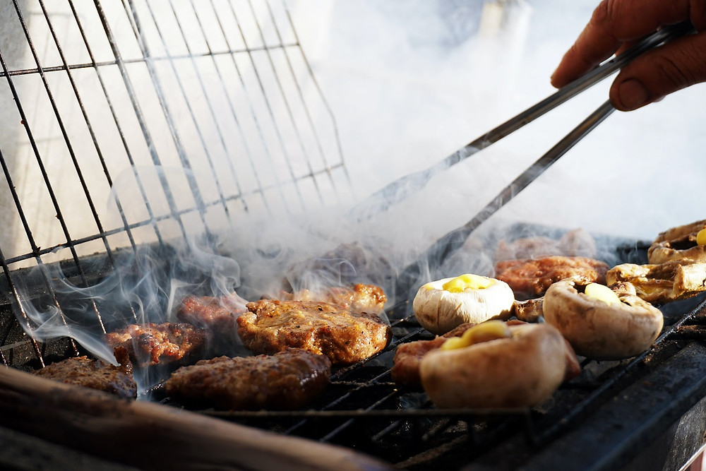 A griller uses tongs to flip food on a grill