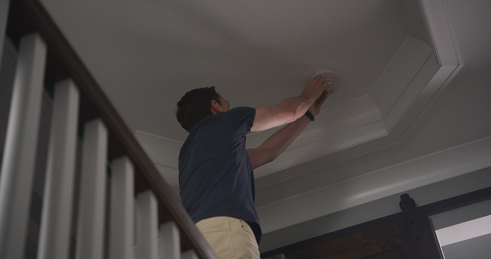A homeowner installs a smoke detector in a foyer