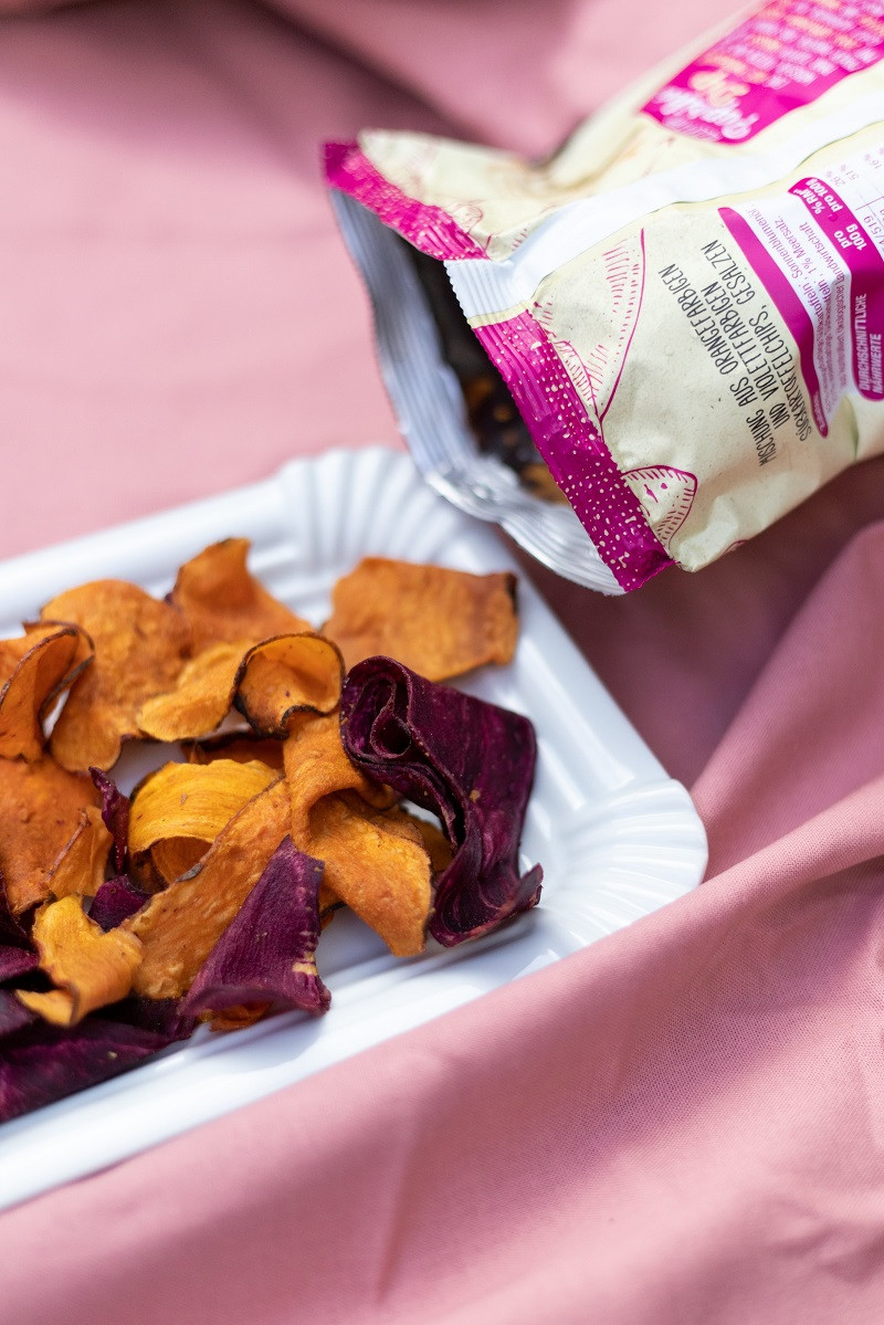 Sweet potato chips rest on a white plate next to its bag