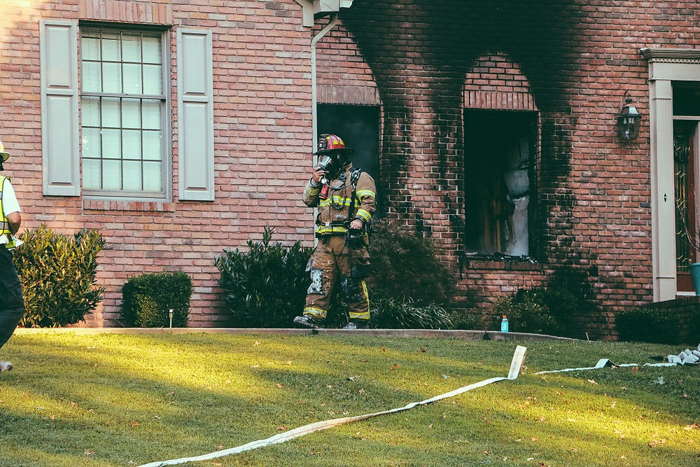 A firefighter walks on a lawn in front of a burned home