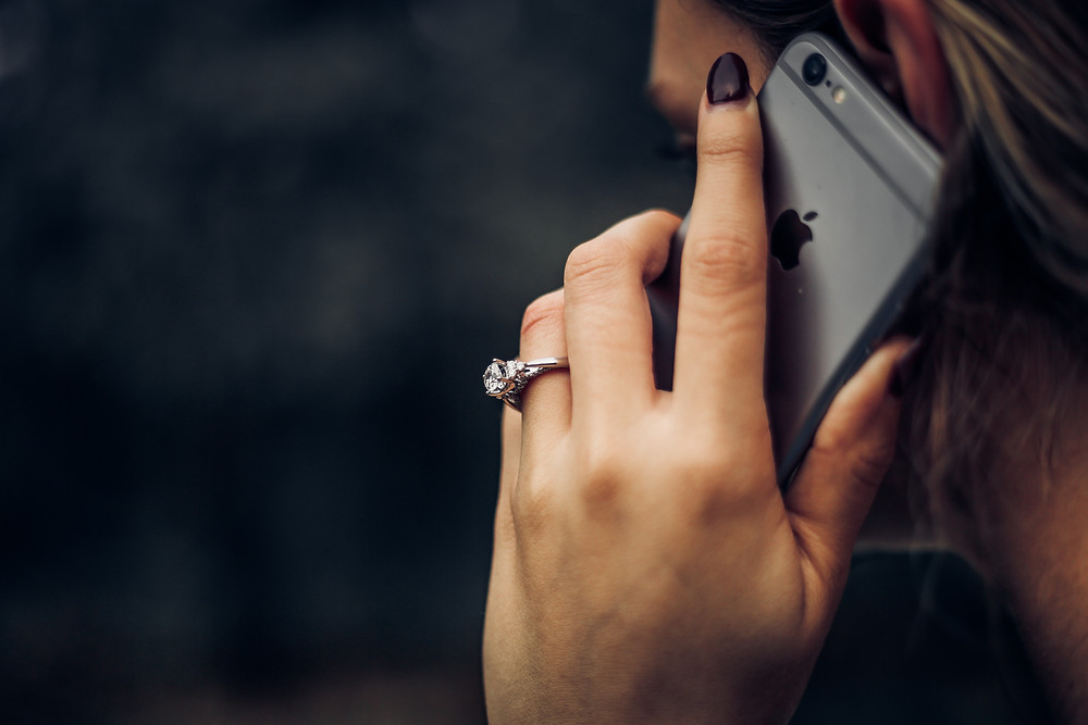 A homeowner holds her cell phone to her ear to speak with her insurance agent.