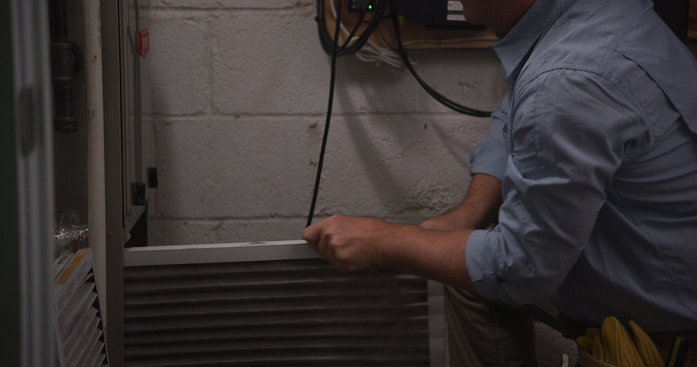 A home service professional changes the air filters in a furnace