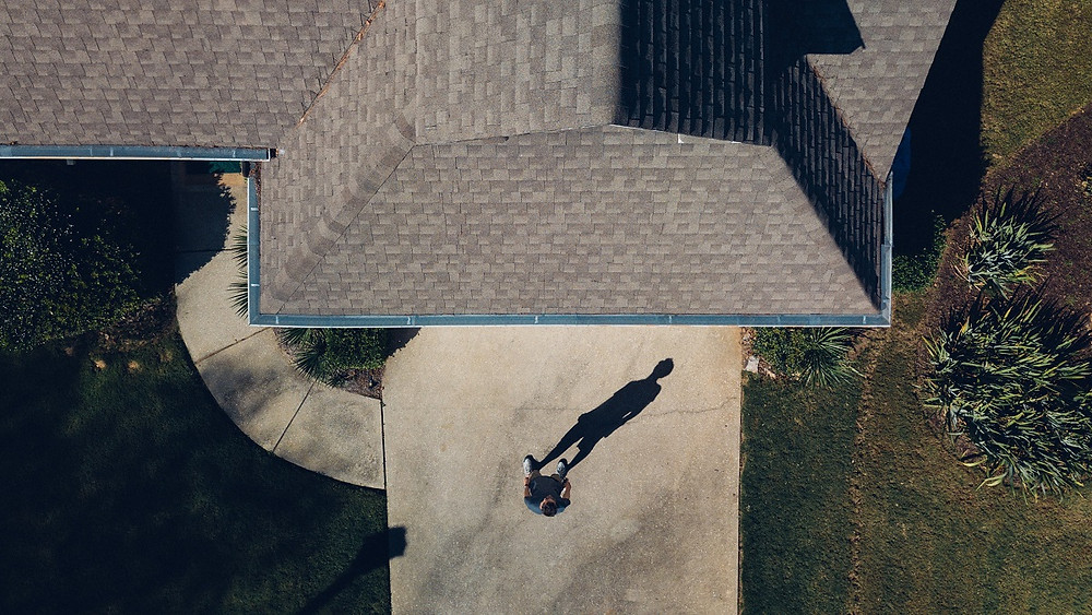A homeowner stands in front of his home, which has a large and well-maintained roof.