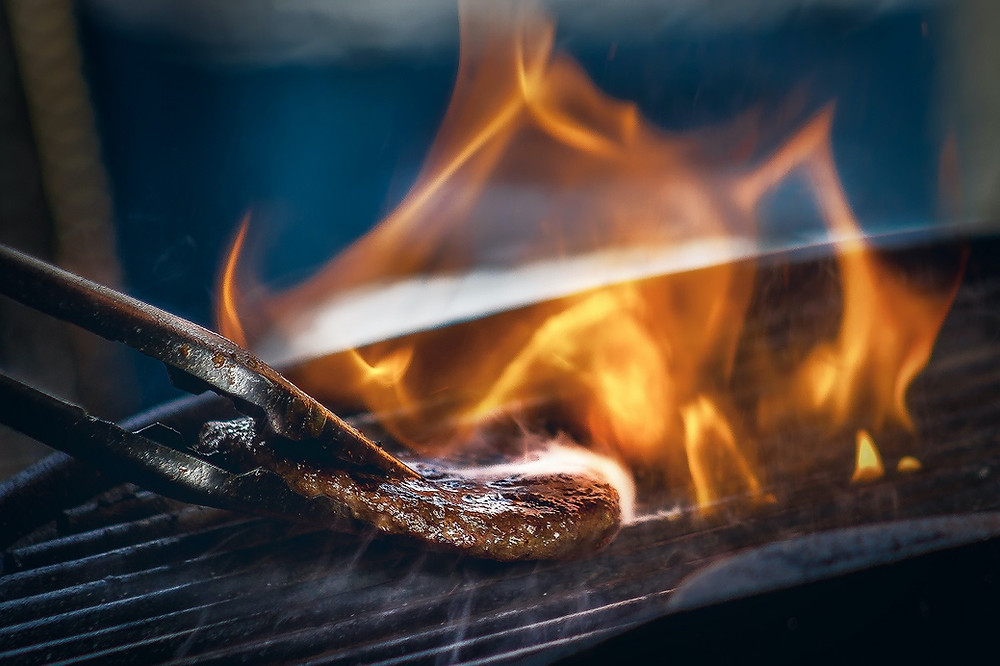 A grill is warm with a fire burning and a steak sizzling on the grates.