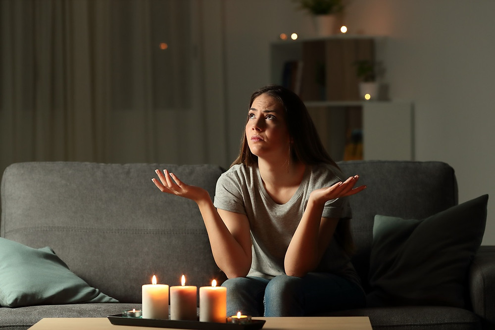 A homeowner sitting on a couch during a blackout throws up her hands in frustration