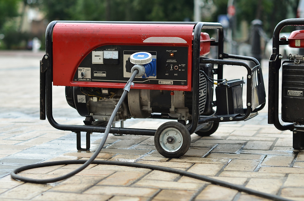 A generator with wires attached to it sits on a brick driveway at least 20 feet away from a home.