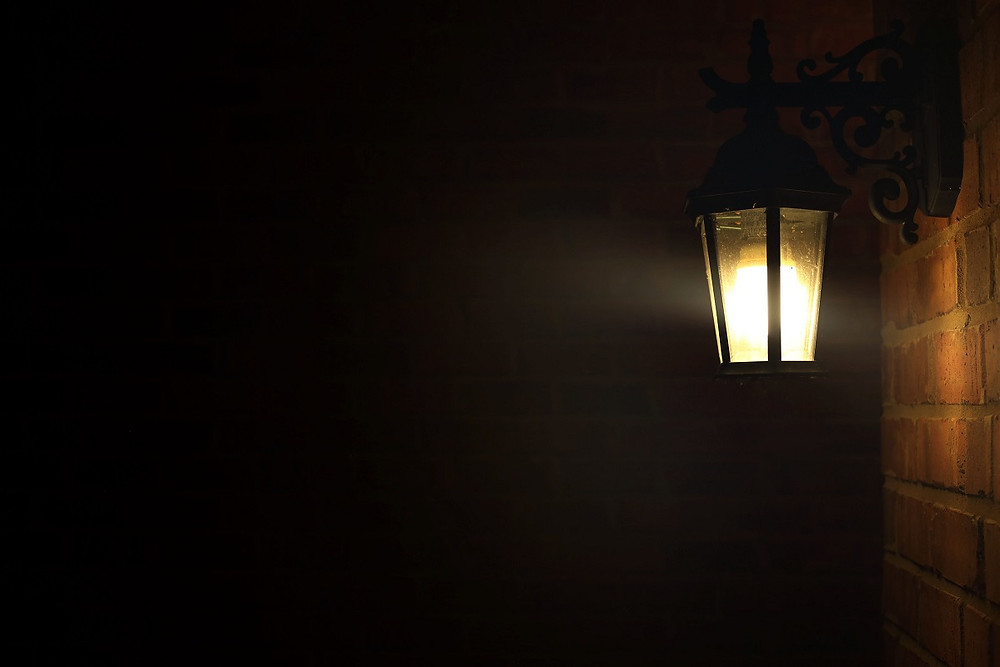 A light on a porch in front of a home is lit.