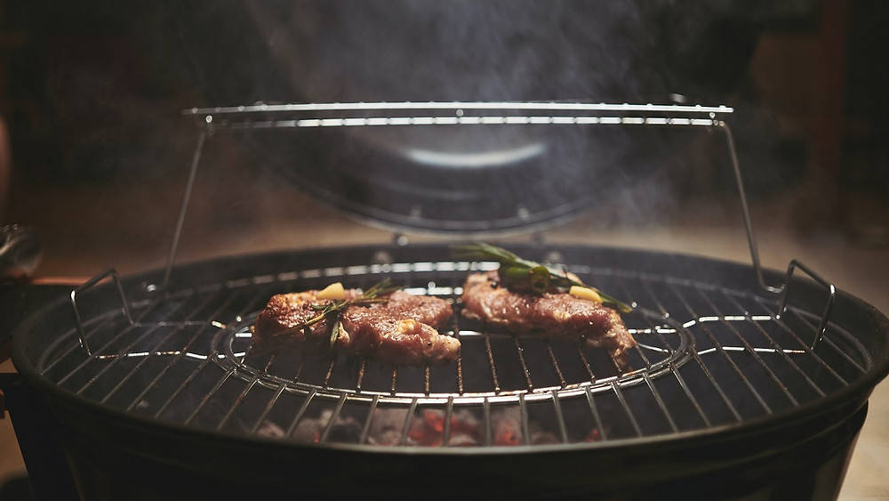 A warm grill with meat on the grates is safely placed with no items around it.