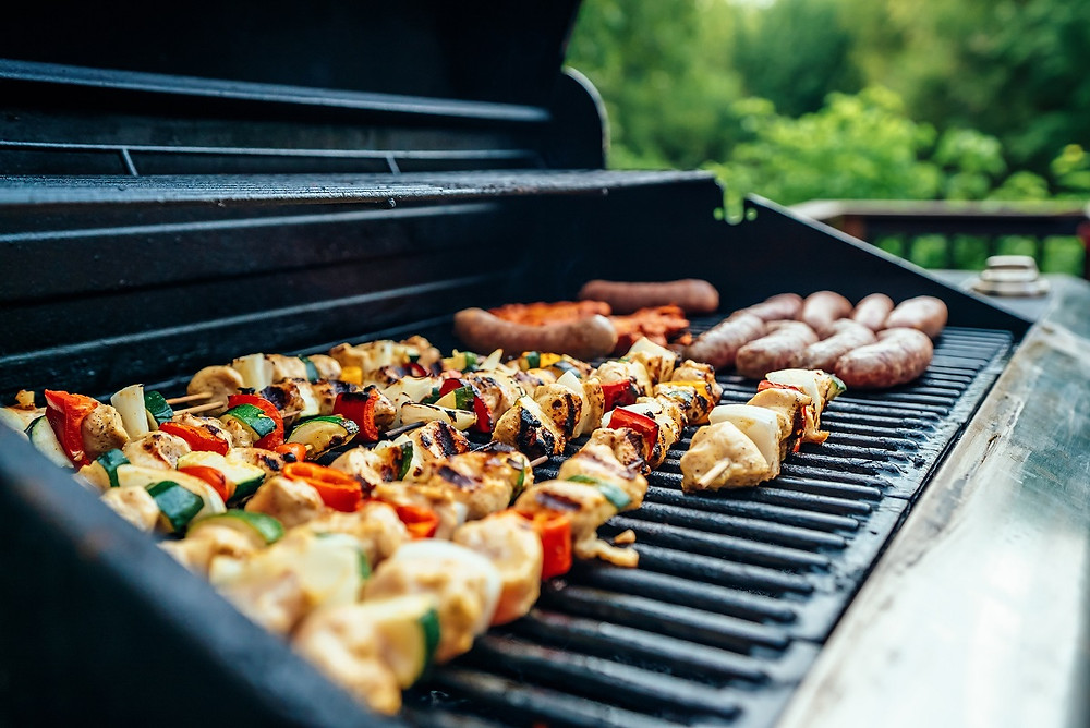 A large grill is open with kebobs cooking on the grates.