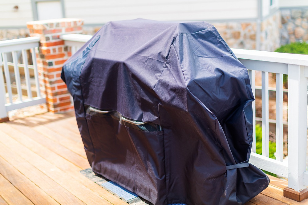 A cover is tightly fitted over a grill to keep it safe from the elements