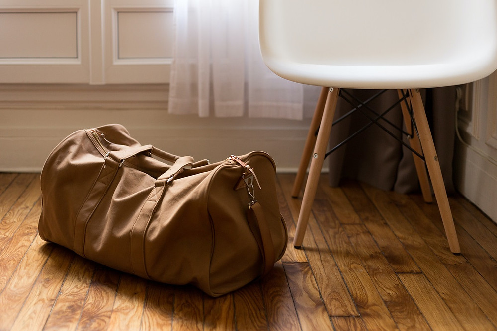 A packed brown duffle next to a table and chair