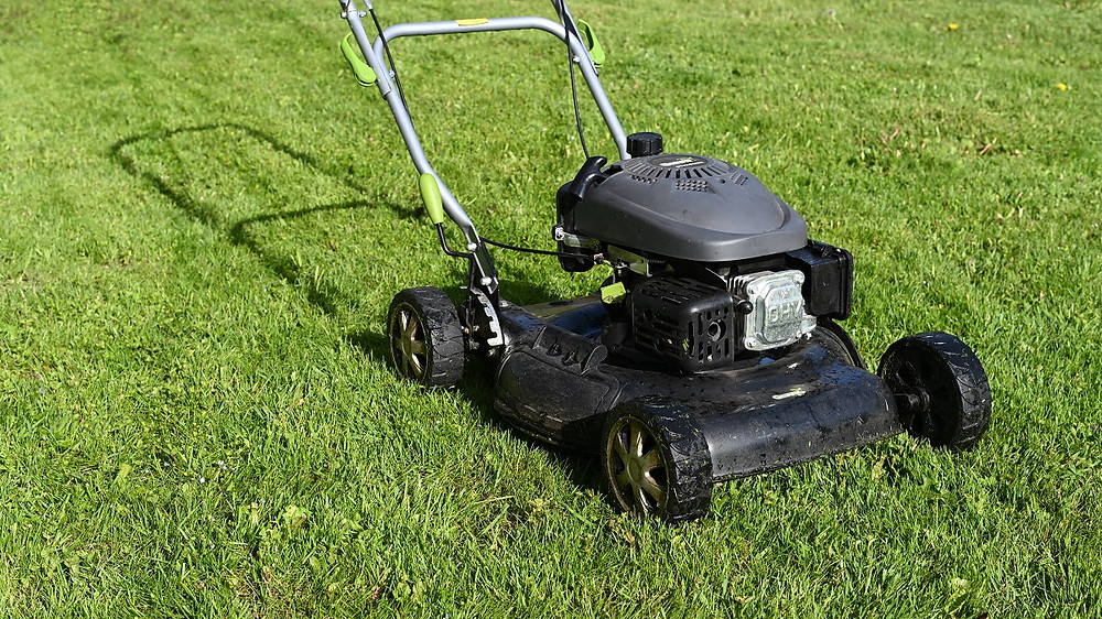 A lawnmower sits on recently cut grass