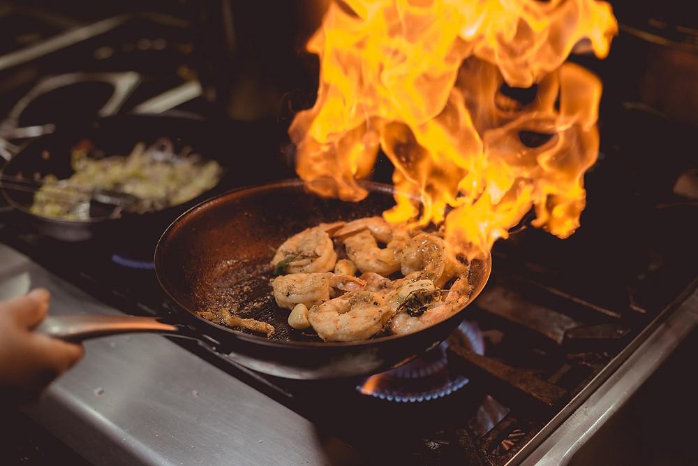 A home chef flambés shrimp in a pan