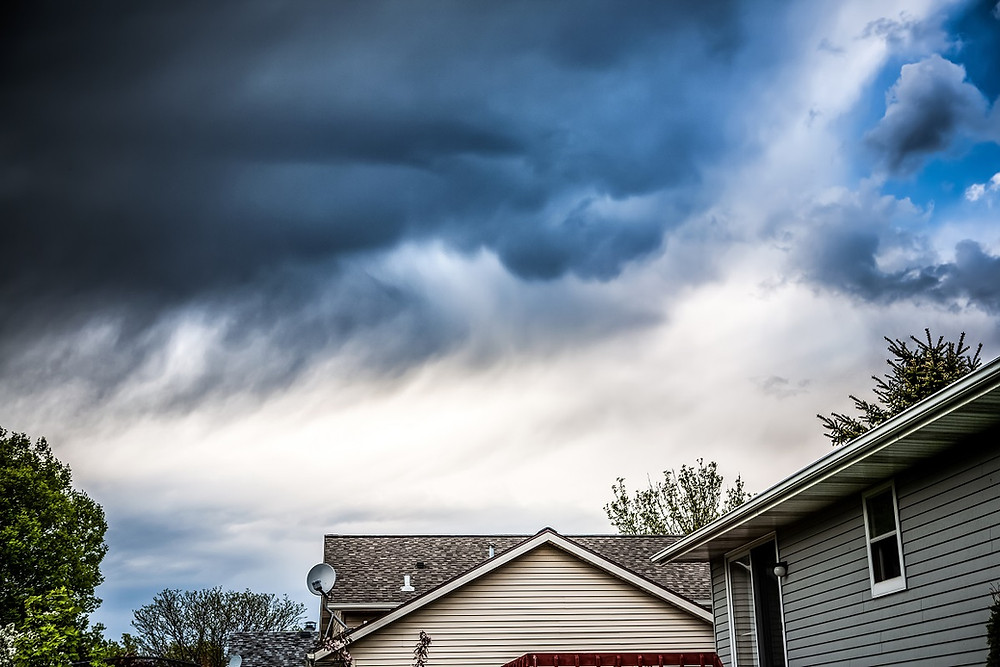 Dark clouds loom over a suburban home.