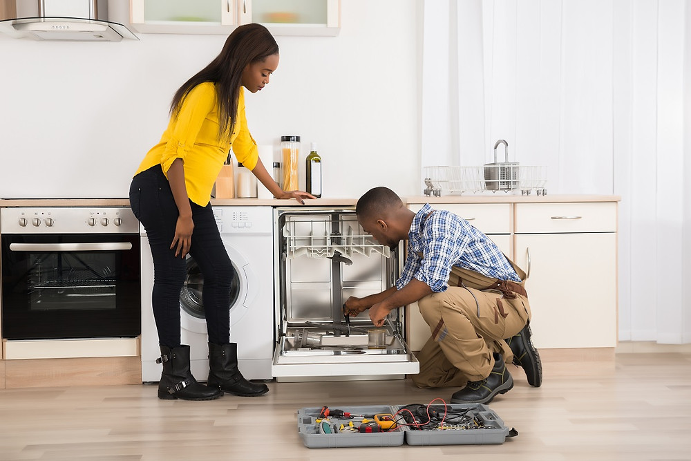 A qualified professional fixes a dishwasher while a homeowner watches