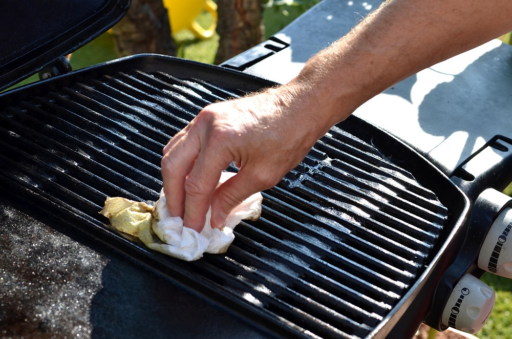 A griller wipes down grates with a paper towel