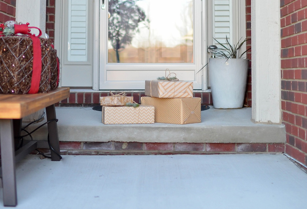 Shipping boxes wait on a concrete porch for a homeowner to pick them up.